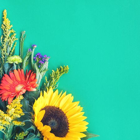 Photo pour Corner border of different fresh bright colorful summer flowers lying on trendy mint background. Flat lay style. Copy space. - image libre de droit