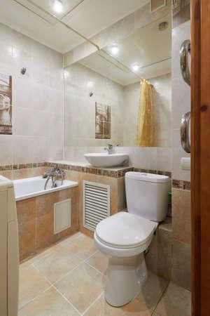 Photo pour Photo of a small toilet room with a toilet, a bathtub and a mirror - image libre de droit