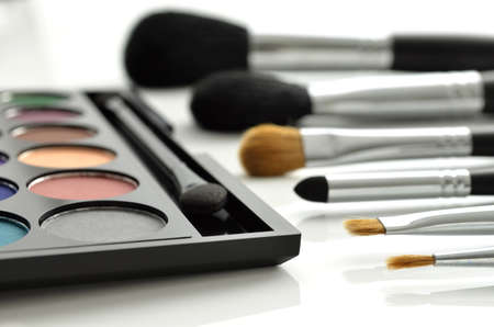 Makeup brushes and eye-shadows palette on white background