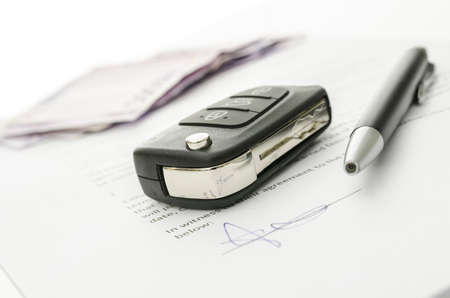 Black car key and money on a signed contract of car sale   Focus on a key