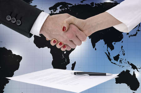 Male and female  hands shaking over signed contract  Business or political concept