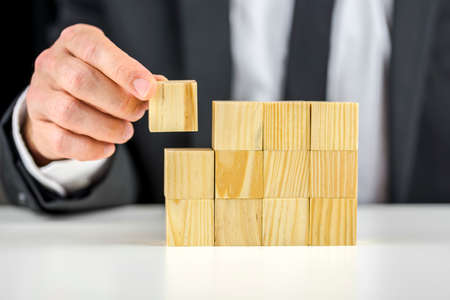Closeup of businessman making a structure with wooden cubes. Building a business concept.