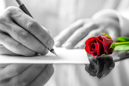 Close up of the hands of a man writing a love letter to his sweetheart with a single romantic red rose with selective colour lying on the desk alongside him