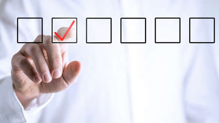 Man ticking a check box in a line of empty boxes on a virtual screen or interface with his finger