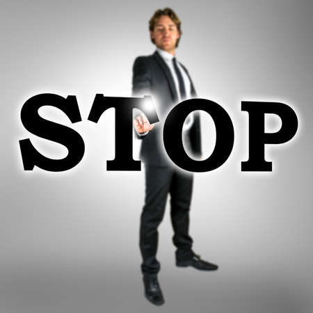 Stop written in large black capital letters on a virtual interface with a stylish businessman in a suit standing behind activating the touchscreen with a finger, conceptual image on a grey background