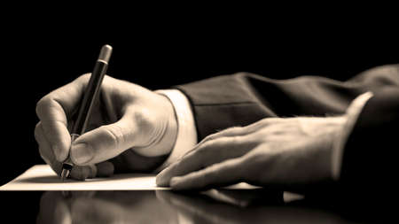 Photo pour Closeup low angle perspective of a businessman in a suit signing a document with a fountain pen as he closes a business deal or finalises a contract or agreement - image libre de droit