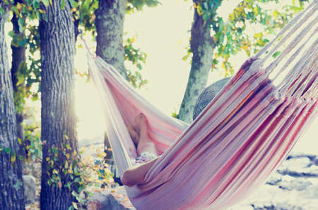 Person relaxing in a hammock in the shade of a tree on a hot summer day, view from behind. With retro filter effect.