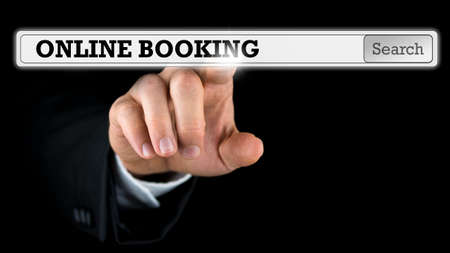 Online booking written in a navigation bar on a virtual interface or computer screen with a businessman reaching out his finger to activate the button from behind.