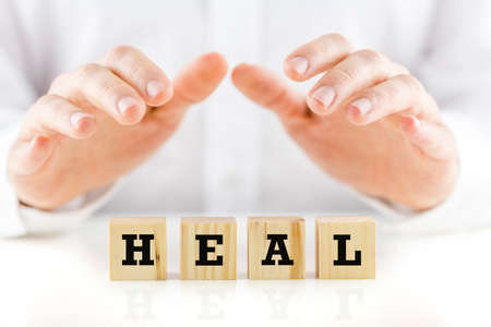 Conceptual image with the word Heal on wooden blocks or cubes protected by the hands of a man sheltering them from above.