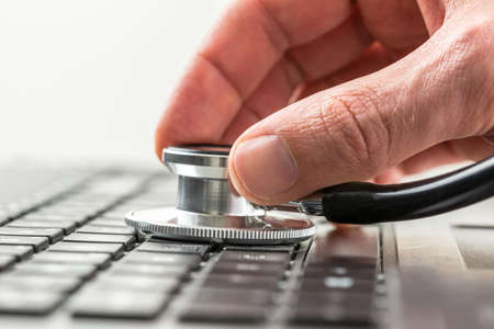 Conceptual image of the hand of a man checking the health of his laptop computer using a stethoscope as he checks for malware and viruses or any electronic malfunctions.