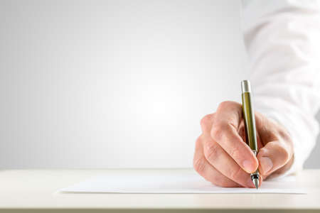 Close-up of a male hand with white sleeve holding a ballpoint in order to start writing on a blank paper placed on the desk