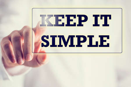 Keep It Simple in a navigation bar on a virtual screen with a businessman touching it to activate it from behind conceptual of simplicity, clarity and easy understanding in business and in life.
