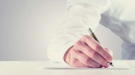 Photo pour Vintage retro style image of a man signing a document or writing notes on a sheet of paper, close up of his hand with copyspace to the left. - image libre de droit
