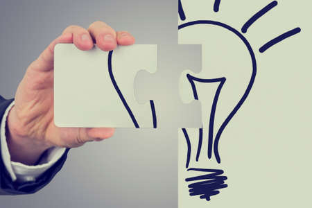 Retro image of businessman with the idea for business development holding two pieces of a jigsaw puzzle bearing the image of a light bulb ready to fit them together to find the perfect idea