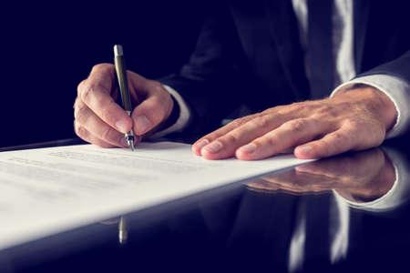 Photo pour Retro image of lawyer signing important legal document on black desk. Over black background. - image libre de droit