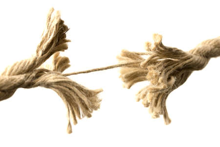 Close-up of a rope splitting apart held together by one last thread, concept of fragility and division, with copy space on white
