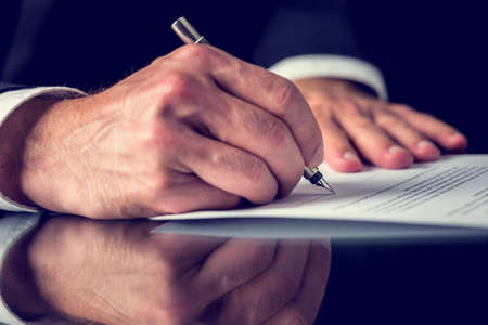 Photo pour Closeup of male hand signing mortgage or other important legal or business document. - image libre de droit