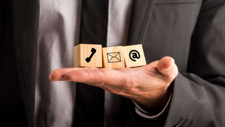 Communications concept with a businessman holding three wooden blocks in his hand depicting a telephone, mail and email for contact, advice , chat and support.