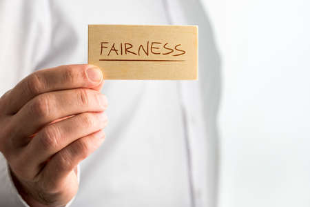 Fairness Concept Design- Close up Human Hand Holding Small Piece Wooden Sign with Underlined Fairness Text over White Shirt.