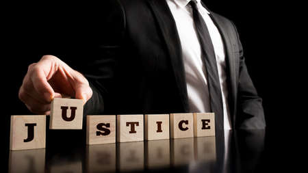 Simple Justice Concept - Close up Businessman in Black Business Suit Arranging Small Wooden Pieces with Justice Text on Black Background.