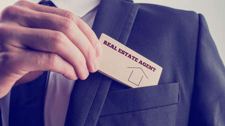 Real Estate Agent in Black Suit Putting Small Wooden Piece with Real Estate Agent Text and Graphic to Front Pocket.