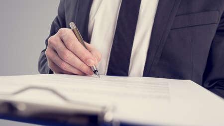 Photo pour Retro vintage style image of a businessman signing a contract or document on a map. - image libre de droit