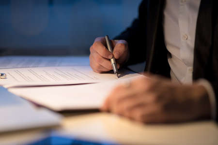 Photo pour Businessman working late signing a document or contract in a dark office with a fountain pen by the light of a lamp, close up view of his hands. - image libre de droit