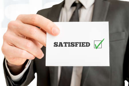 Customer feedback - Satisfied - concept with a businessman holding up a card with a ticked check box from a survey or feedback report and the word Satisfied, close up of his hand.