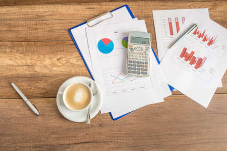 Overhead view of paperwork and graphs spread out with a calculator and cup of coffee on a wooden business desk.