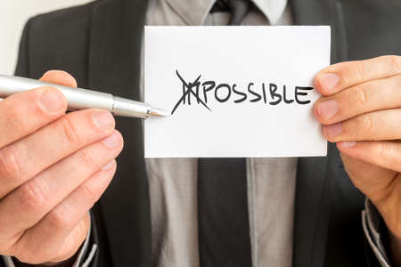 Man crossing through the Im in the handwritten word Impossible on a white business card with a metallic fountain pen in a concept of opposites for Impossible - Possible.