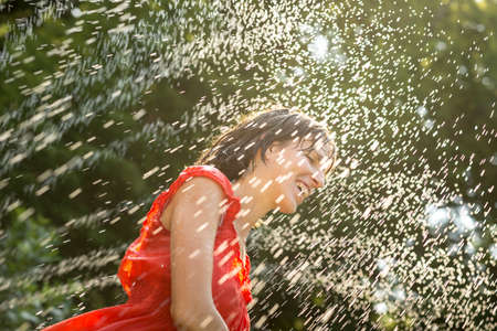 Laughing woman cooling off under a spray of water in her orange summer dress on a hot day against a backdrop of green trees.