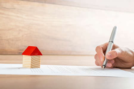 Photo pour Closeup of new homeowner signing a contract of house sale or mortgage papers with a wooden toy house on the document. Suitable for real estate concept. - image libre de droit