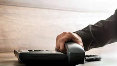 Male hand with black sleeve suit picking up the receiver of an office telephone, with copy space on rustic wooden background. Concept of customer support, global communication and telemarketing.