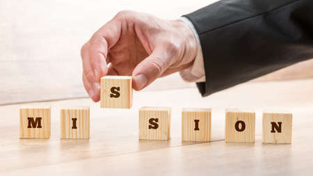 Closeup of businessman creating a word Mission with seven wooden cubes. Conceptual of business vision, aim and strategy.