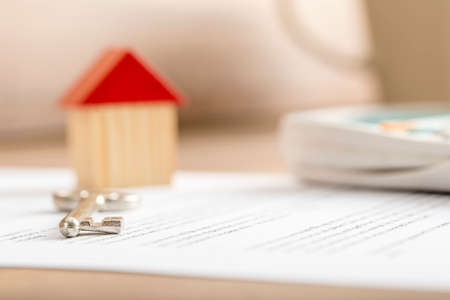 Photo pour Closeup of contract of house sale ready to be signed with wooden toy house, house key and calculator on it. Conceptual of real estate, mortgage and lease. - image libre de droit