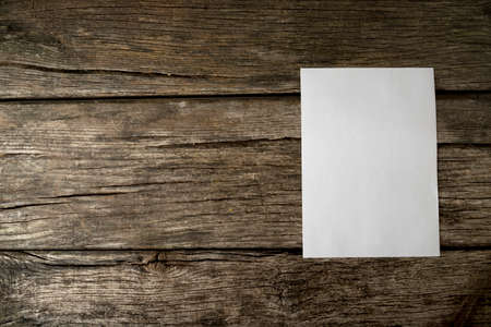 Blank sheet of white paper with copyspace for your text on old textured rustic wooden boards with additional copyspace to the left.