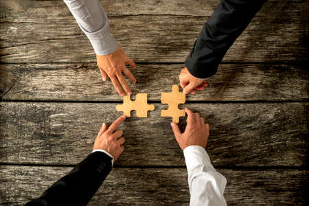 Foto de Four successful business men joining two puzzle pieces each being held by two partners, rustic wooden background. Conceptual of merger or creative cooperation of two business companies. - Imagen libre de derechos