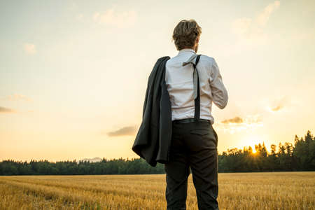 Young successful businessman standing in wheat field looking gazing into the future as he decides upon new steps and directions to take in his career.