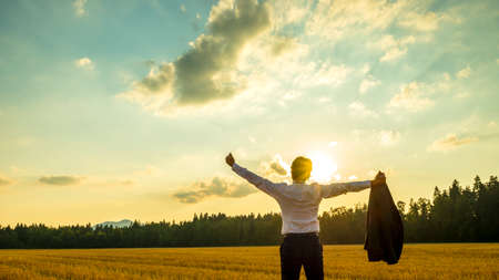 Young ambitious executive enjoying and celebrating his business success as he stands in beautiful nature under majestic sky with his arms spread widely holding his thumbs up.