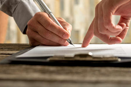 Photo for Closeup of businessman showing his new business partner where to sign an agreement or contract with fountain pen  on rustic wooden desk. - Royalty Free Image