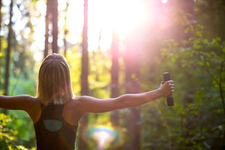 Foto de Young blonde woman working out with dumbbells in beautiful nature with her back to the camera and arms widely spread. Conceptual of exercise and body care. - Imagen libre de derechos