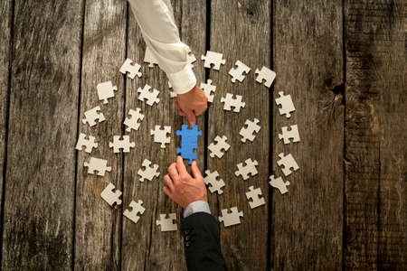 Foto de Teamwork in business concept with two businessmen around a circle of scattered white puzzle pieces cooperating to construct a blue jigsaw in the centre, close up of their hands and wooden table. - Imagen libre de derechos