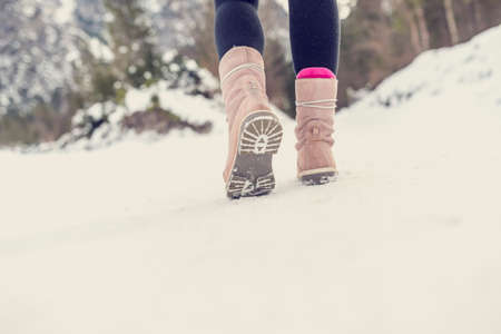 Active woman walking away from the camera through winter snow wearing pale pink boots in the countryside, with copyspace in the foreground. Retro filter effect.の写真素材