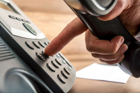Closeup of male hand dialing a telephone number on black landline phone in a global communication concept.