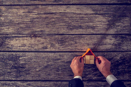 Vision of new home - overhead view of architect or real estate agent placing a roof on top of house miniature made of many wooden cubes on textured wooden planks.