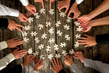 Foto de Teamwork Concept - High Angle View of Businessmen Hands Forming Circle and Holding Puzzle Pieces on Top of a Rustic Wooden Table. - Imagen libre de derechos