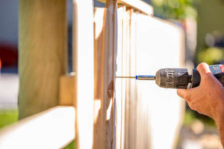 Man erecting a wooden fence outdoors using a handheld electric drill to drill a hole to attach an upright plank, close up of his hand and the tool in a DIY concept.