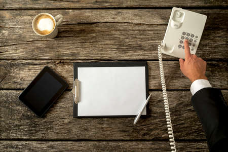 Top view of businessperson making a call with his office phone with digital tablet and blank piece of paper on a rustic wooden desk. Concept of telemarketing, feedback and customer support.