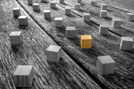 Foto de Conceptual Brown Wooden Block Surrounded by Other Blocks in Monochrome on Top of a Rustic Table. - Imagen libre de derechos