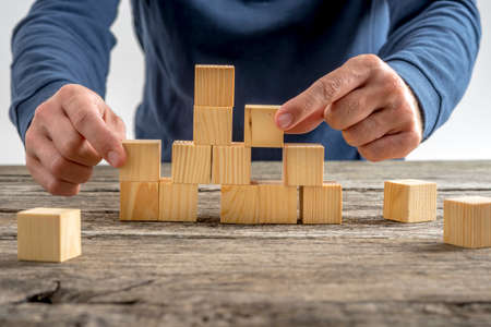 Close up Man Assembling a Tower Using Wooden Cubes on Top of a Rustic Table.